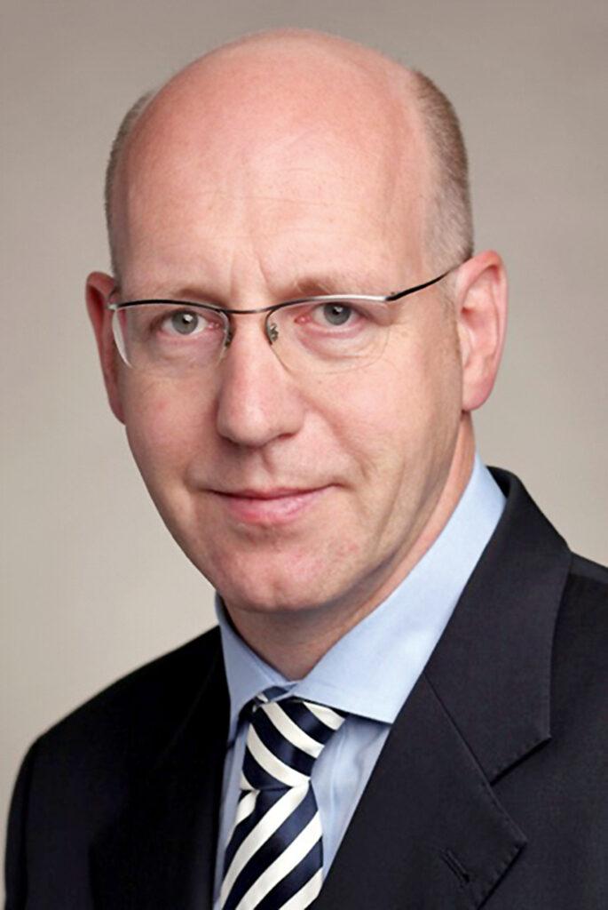 Portrait von IBG-Geschäftsführer Josef Schulze Sutthoff in dunklem Anzug und Krawatte.