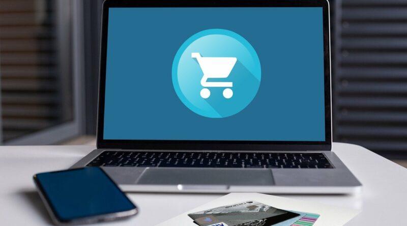 Vor einem Laptop, das auf dem Bildschirm ein Symbol zum Thema E-Commerce zeigt, liegen ein Smartphone und EC- und Kreditkarten, um das Thema Online-Handel zu symobilisieren.