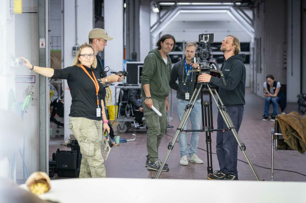 """2020 produzierte Olaf Levin (Mitte) für das Autohaus Hotz und Heitmann den Kurzfilm """"Take Five"""" mit Starbesetzung. Dafür verwandelte die Filmburg die Geschäftsräume des Unternehmens in ein Filmstudio."""