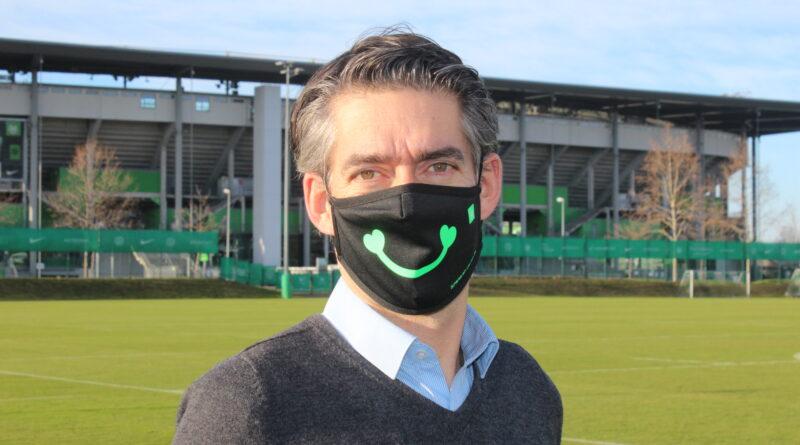 Michael Meeske, Geschäftsführer der VfL Wolfsburg-Fußball GmbH, trägt die Schenke-ein-Lächeln Maske des VfL