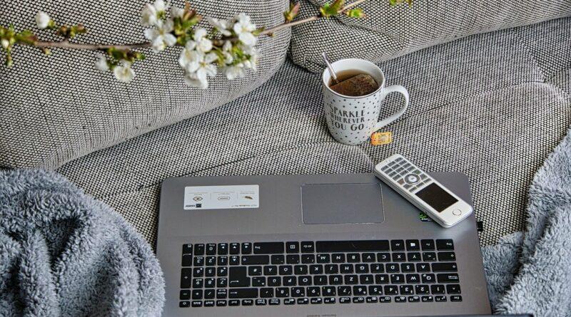 New Work als Beispiel für das Homeoffice - Eine Couch mit einer Kuscheldecke, dem Laptop, einem Telefon und einer Tasse Tee