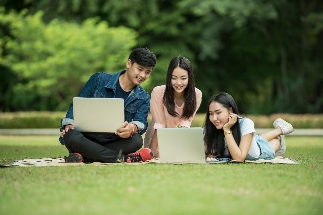 42Wolfsburg: Symbolisch sitzen drei Studenten mit ihren geöffneten Laptops auf einer Wiese