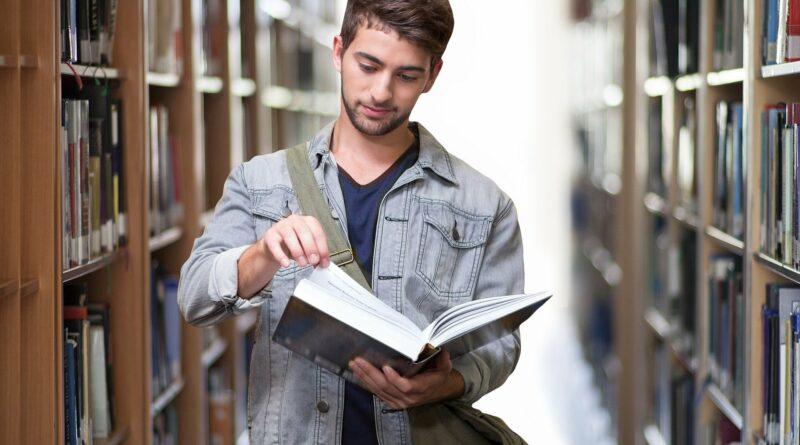 Symbolbild zum Thema Masterplan Hochschule und Wissenschaft. Das Bild zeigt einen Studenten mit einem Buch in einer Bibliothek.