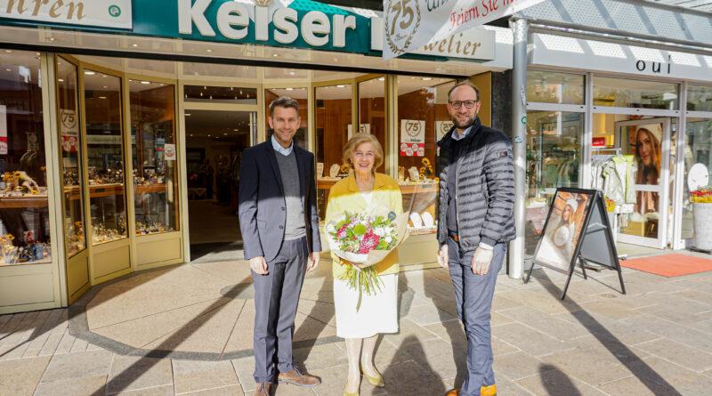 Oberbürgermeister Dennis Weilmann (links) gratuliert gemeinsam mit WMG-Geschäftsführer Jens Hofschröer (rechts) Inhaberin Brunhilde Keiser zum 75. Jubiläum von Uhren Keiser